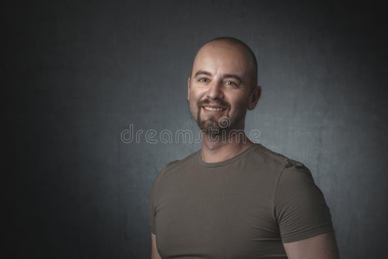 Porträt des lächelnden kaukasischen Mannes mit T-Shirt und dunklem Hintergrund stockfoto