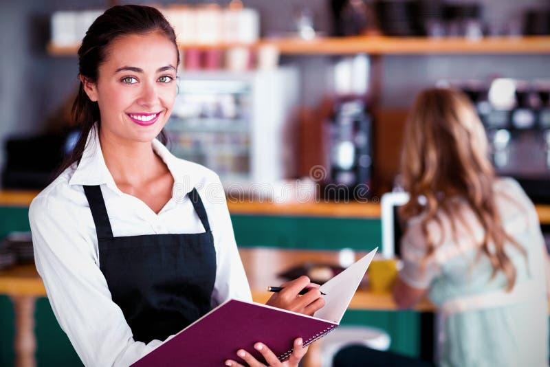 Porträt des lächelnden Kellnerinschreibens in einer Datei lizenzfreies stockfoto