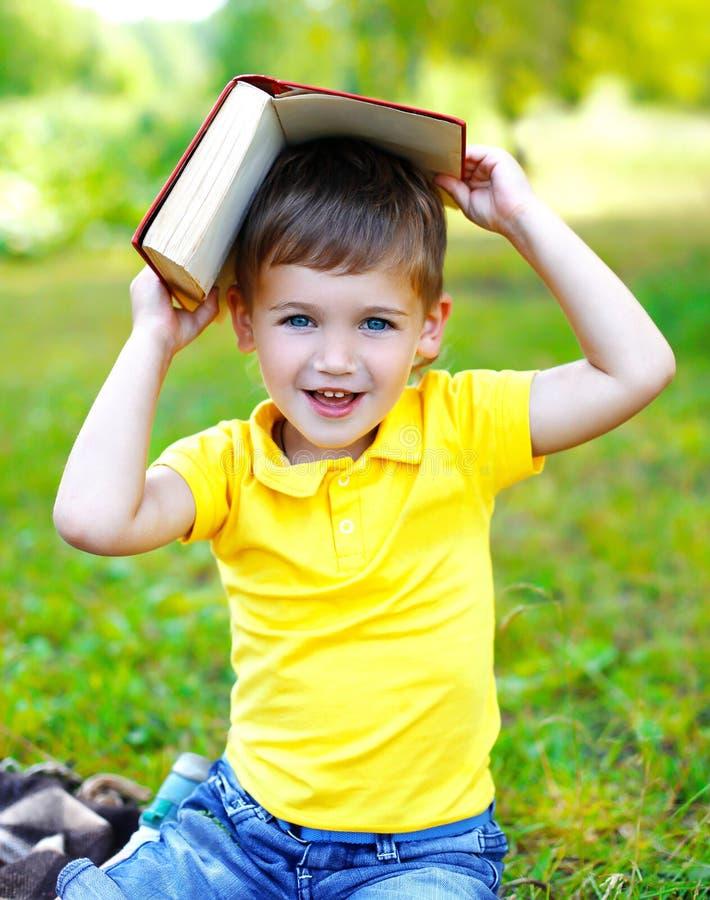 Porträt des lächelnden Kinderjungen mit Buch auf dem Gras im Sommer stockfotografie