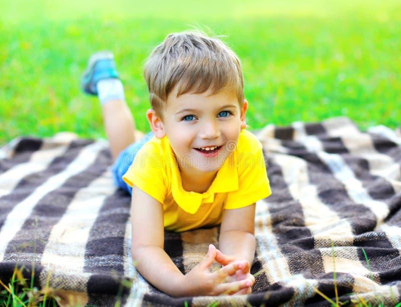 Porträt des lächelnden Kindes des kleinen Jungen, das auf dem Gras liegt lizenzfreies stockfoto