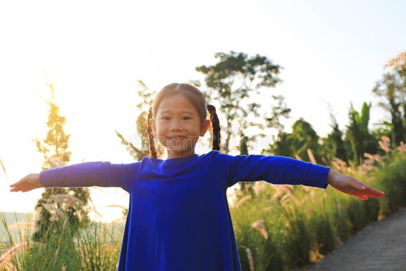 Porträt des lächelnden kleinen asiatischen Kindermädchens öffnete ihre Arme auf dem Gebiet bei Sonnenuntergang stockbild