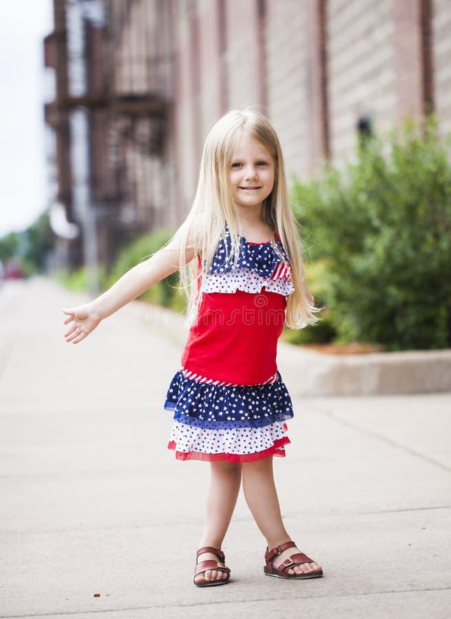 Porträt des lächelnden kleinen Mädchens, das auf Straße geht stockbilder