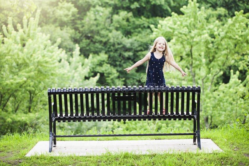 Porträt des lächelnden kleinen Mädchens, das draußen auf Bank steht stockbild