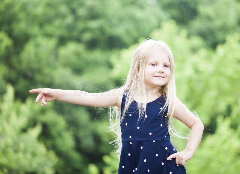 Porträt des lächelnden kleinen Mädchens, das draußen aufwirft stockfotografie