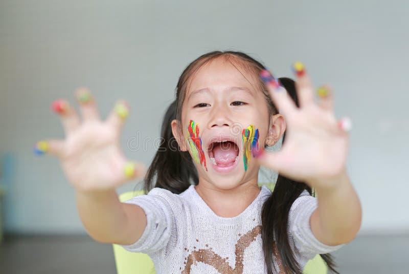 Porträt des lächelnden kleinen Mädchens, das durch ihre bunten Hände und Backe gemalt im Kinderraum schaut Fokus am Babygesicht stockbild