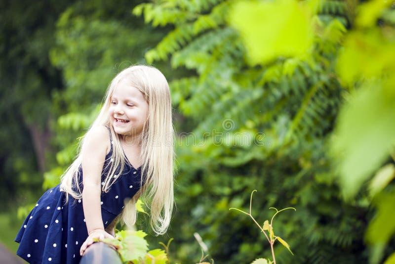 Porträt des lächelnden kleinen Mädchens, das in Park geht stockfotografie