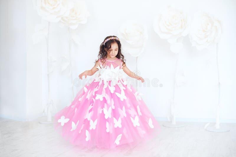 Porträt des lächelnden kleinen Mädchens im Prinzessinrosakleid mit Schmetterlingen lizenzfreie stockbilder