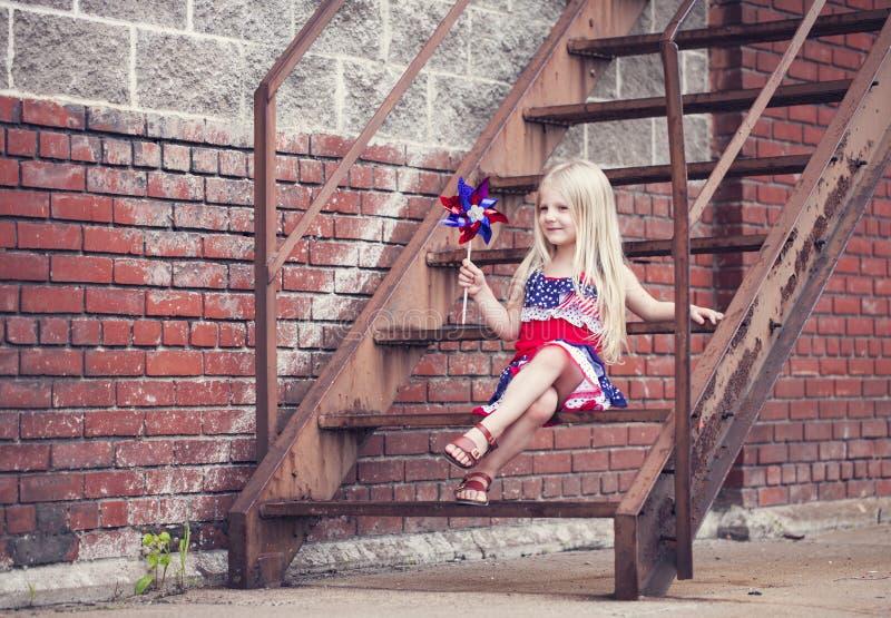 Porträt des lächelnden kleinen Mädchens mit dem Feuerrad, das auf Treppe sitzt stockbilder