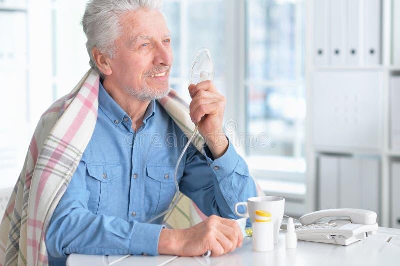 Porträt des lächelnden kranken älteren Mannes mit Inhalator lizenzfreie stockfotos
