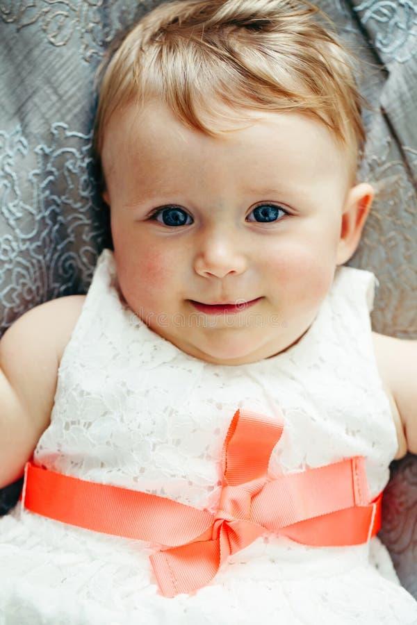 Porträt des lächelnden lachenden Babys des netten entzückenden Kaukasiers mit blauen Augen im weißen Kleid mit dem roten Bogen, d stockfoto