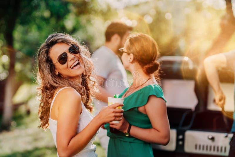 Porträt des lächelnden Mädchens, glückliche Frau, die Sonntag mit Freunden an der Grillpartei genießt stockbild