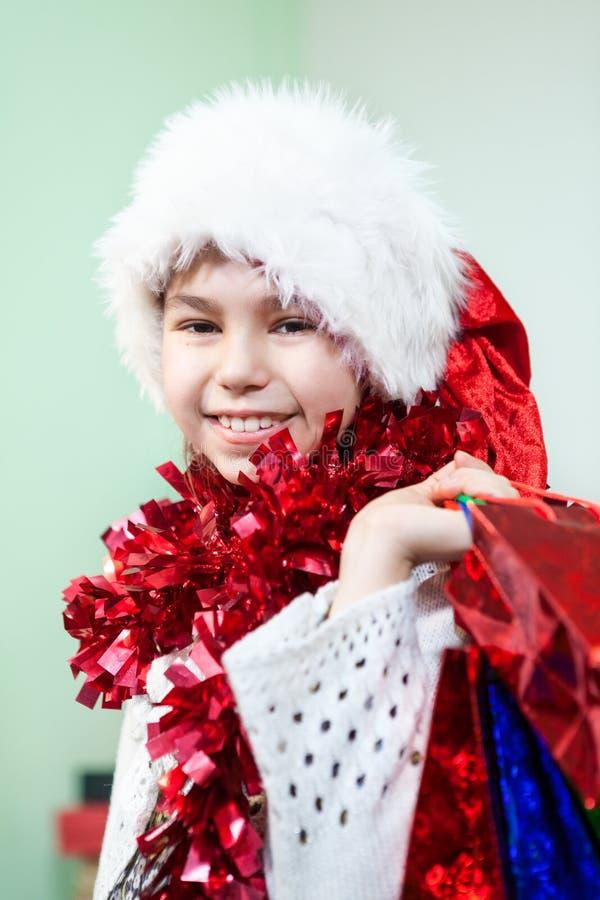 Porträt des lächelnden Mädchens im roten Lametta und Sankt-Hut mit Geschenk bauschen sich in der Hand und betrachten Kamera stockfoto