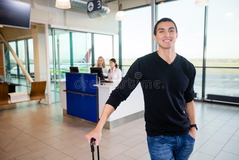 Porträt des lächelnden männlichen Passagiers am Flughafen lizenzfreies stockfoto