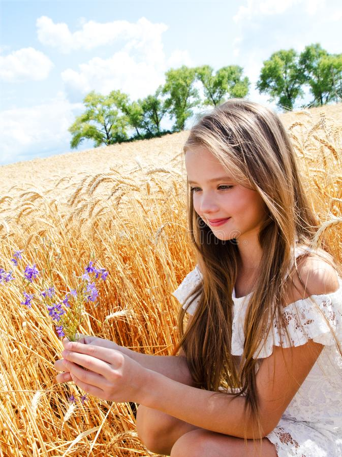 Porträt des lächelnden netten Kindes des kleinen Mädchens auf dem Feld des Weizens Blumen halten lizenzfreie stockfotografie