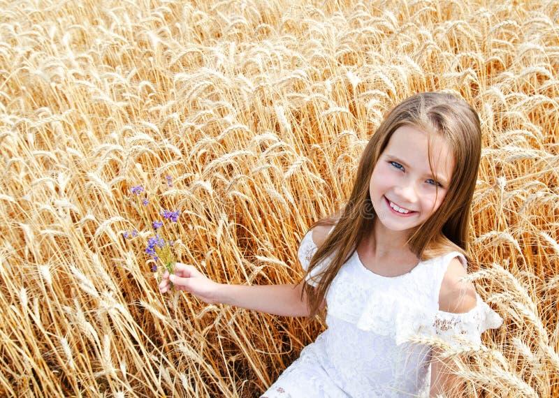 Porträt des lächelnden netten Kindes des kleinen Mädchens auf dem Feld des Weizens Blumen halten lizenzfreie stockbilder