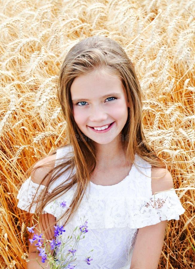 Porträt des lächelnden netten Kindes des kleinen Mädchens auf dem Feld des Weizens Blumen halten stockbilder