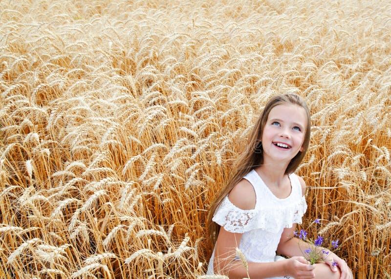 Porträt des lächelnden netten Kindes des kleinen Mädchens auf dem Feld des Weizens Blumen halten lizenzfreies stockbild