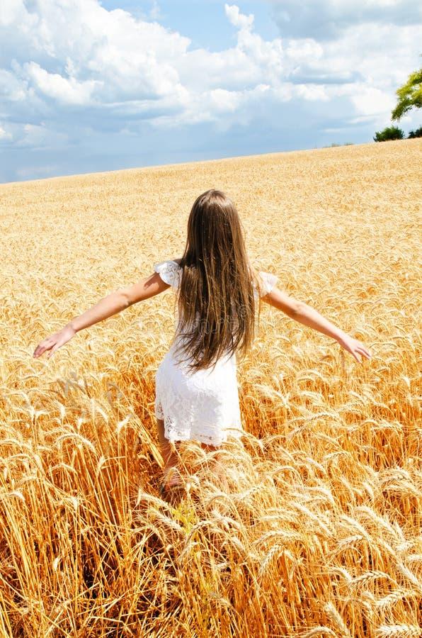 Porträt des lächelnden netten Kindes des kleinen Mädchens, das durch Feld des Weizens läuft lizenzfreie stockbilder