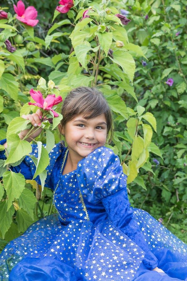 Porträt des lächelnden netten kleinen Mädchens an blühendem Hibiscus lizenzfreie stockfotos