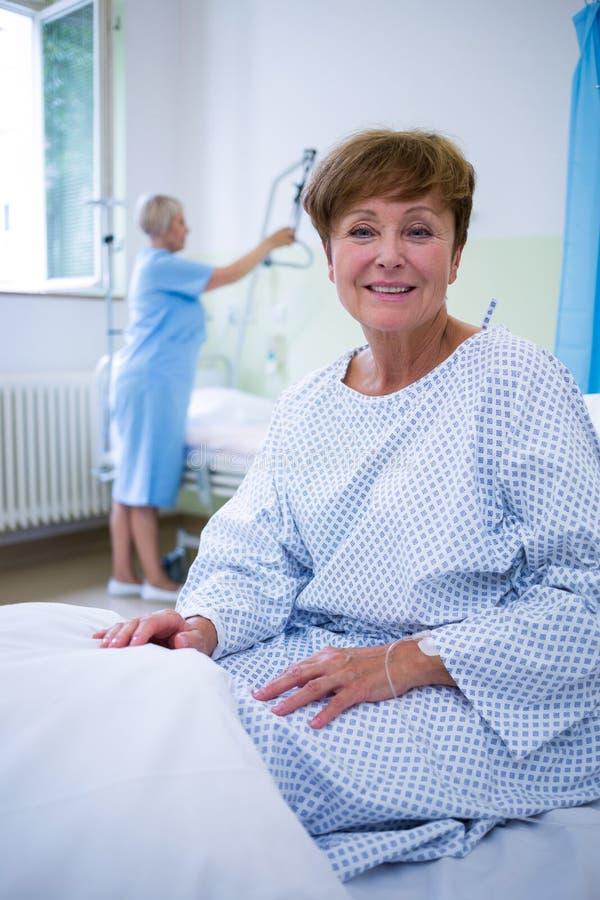 Porträt des lächelnden Patienten sitzend auf Bett stockfotografie