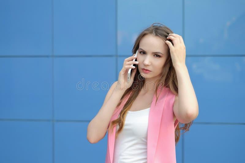 Porträt des lächelnden schönen Abschlusses der jungen Frau oben mit dem Handy im Freien stockfotos