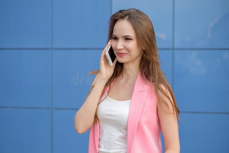Porträt des lächelnden schönen Abschlusses der jungen Frau oben mit dem Handy im Freien lizenzfreies stockfoto