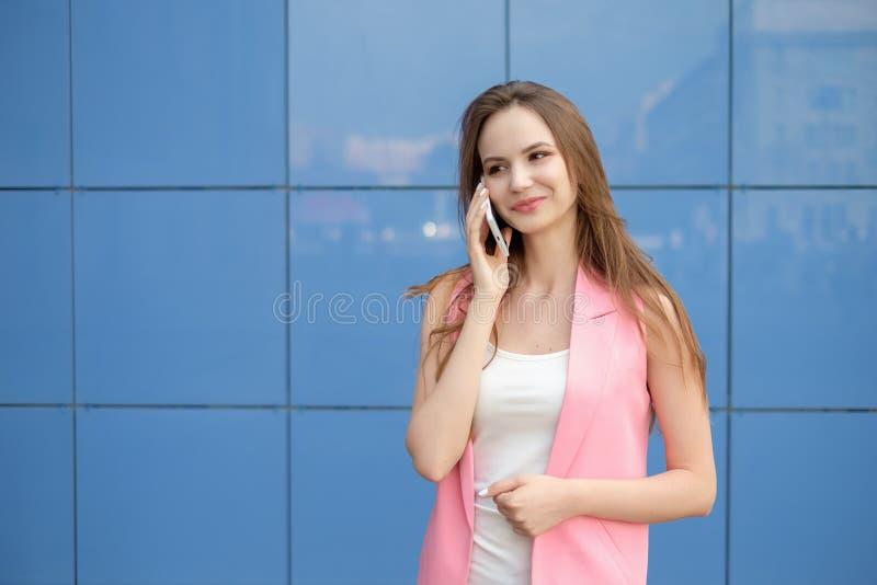 Porträt des lächelnden schönen Abschlusses der jungen Frau oben mit dem Handy im Freien stockbild