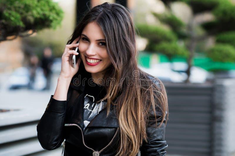 Porträt des lächelnden schönen Abschlusses der jungen Frau oben mit Handy, gegen Hintergrundsommer-Grünstraße stockfoto