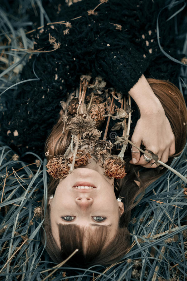 Porträt des lächelnden schönen Mädchens, das auf grünem Gras liegt Lächelndes junges Mädchen, das auf den Nahaufnahmeumarmungsblu lizenzfreie stockfotografie