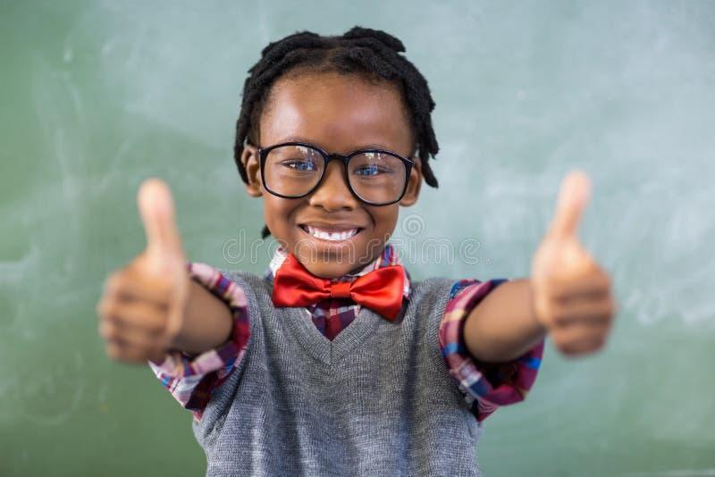 Porträt des lächelnden Schülers Daumen oben im Klassenzimmer zeigend lizenzfreies stockfoto