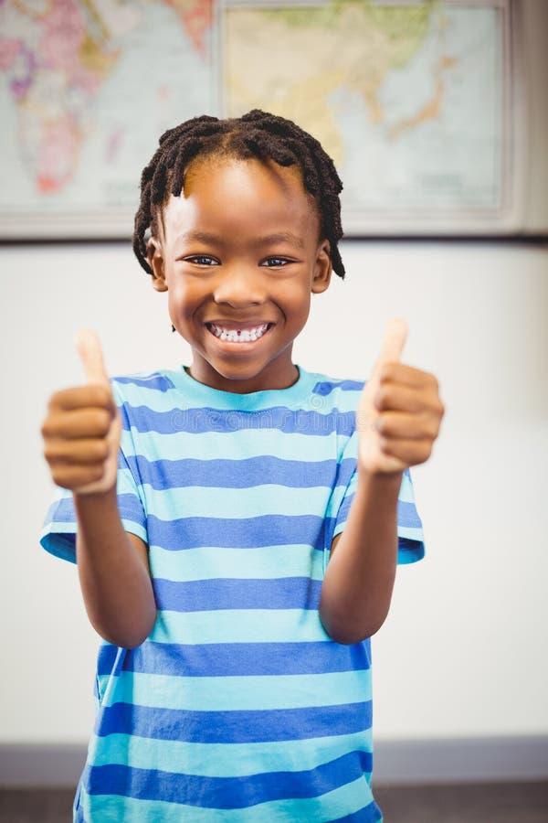 Porträt des lächelnden Schülers Daumen oben im Klassenzimmer zeigend lizenzfreie stockfotos