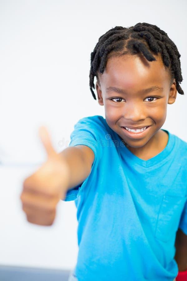 Porträt des lächelnden Schülers Daumen zeigend lizenzfreie stockfotografie