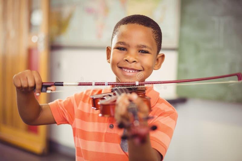 Porträt des lächelnden Schülers Violine im Klassenzimmer spielend stockfoto