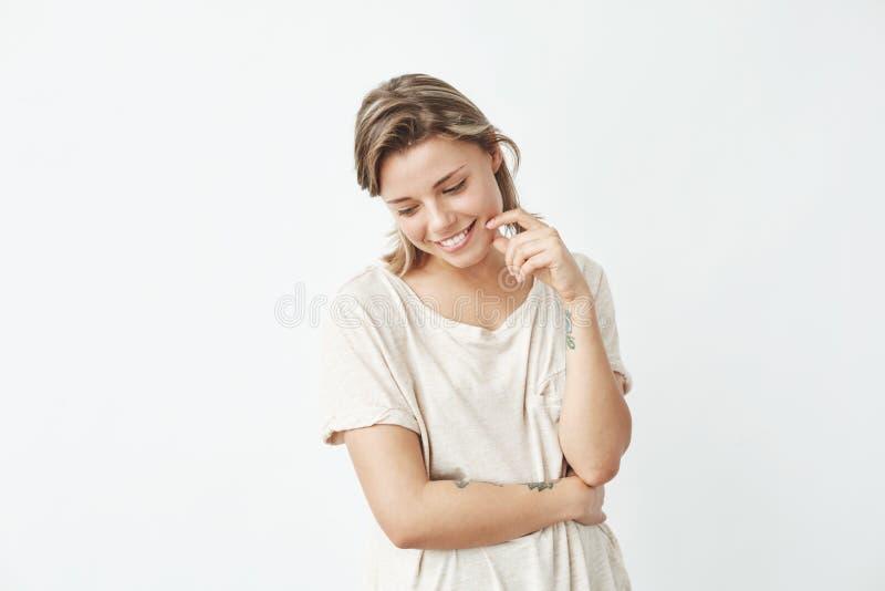 Porträt des lächelnden Schauens des jungen schönen schüchternen Mädchens unten über weißem Hintergrund stockbild