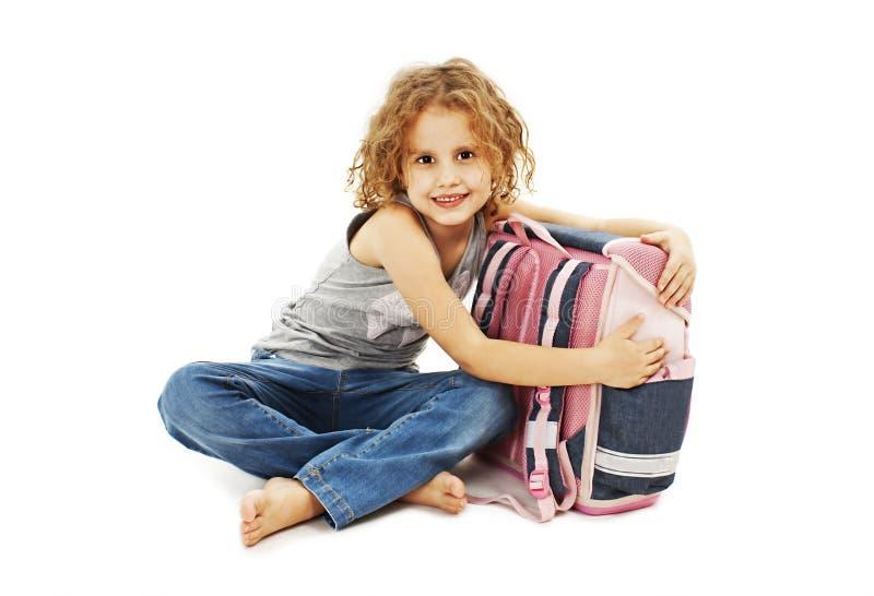 Porträt des lächelnden Schulmädchens, das Rucksack umarmt stockbilder