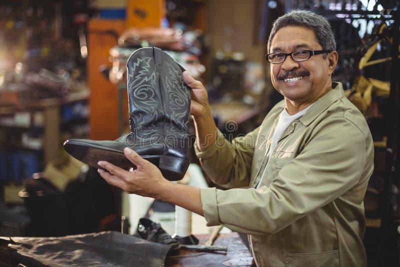 Porträt des lächelnden Schusters einen Lederstiefel halten lizenzfreie stockfotografie