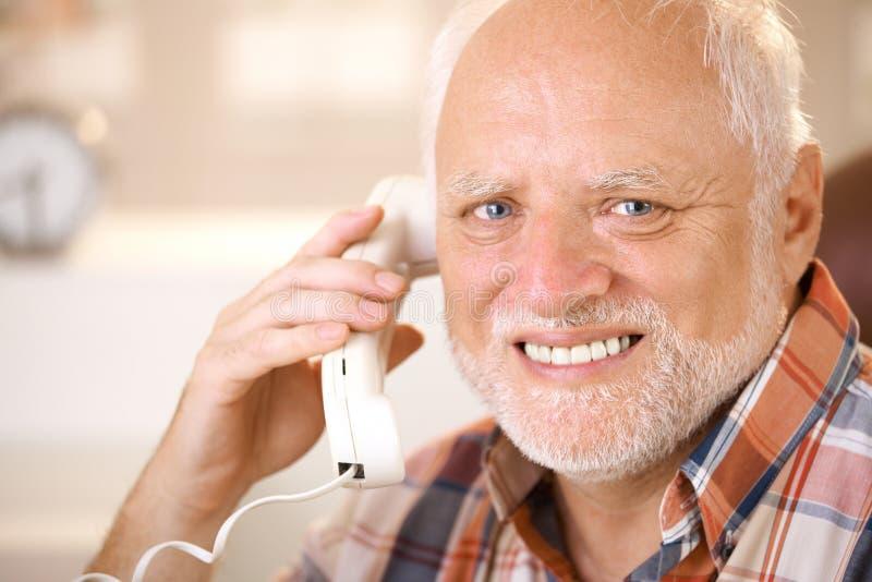 Porträt des lächelnden Seniors, der Überlandleitungstelefon verwendet stockbilder