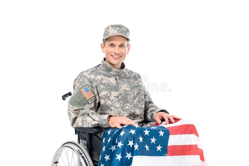 Porträt des lächelnden Soldaten im Rollstuhl mit der amerikanischen Flagge, die Kamera betrachtet stockfotos