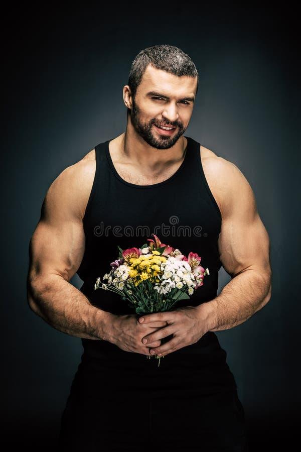 Porträt des lächelnden sportiven Mannes mit Blumenstrauß von Blumen in den Händen lizenzfreie stockfotografie