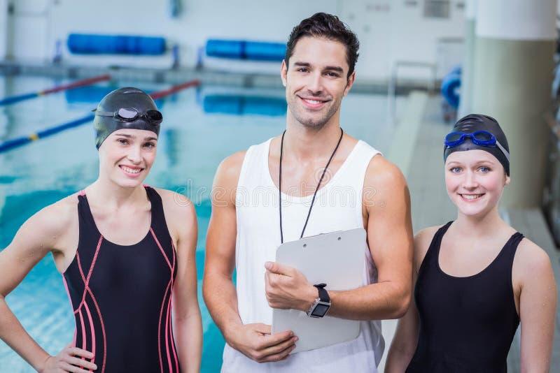 Porträt des lächelnden Trainers und der Schwimmer lizenzfreie stockbilder