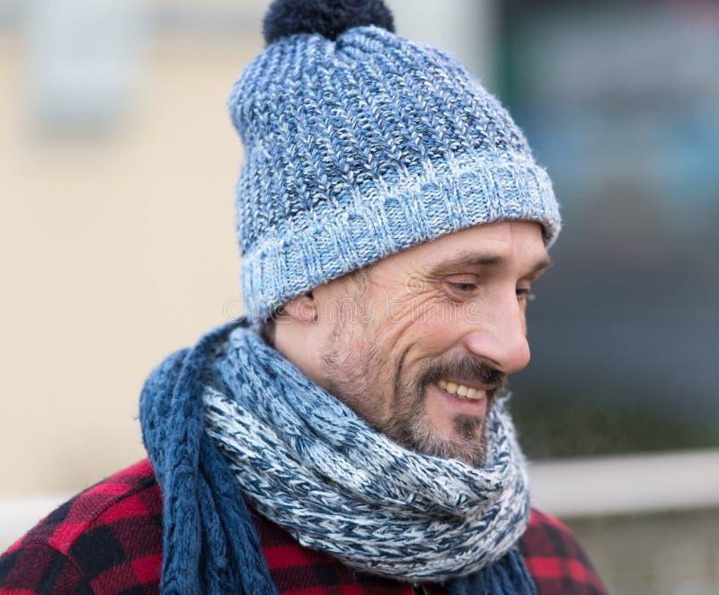 Porträt des lächelnden weißen Kerls auf Straße Weißer Mann in der Winterstrickmütze und -schal Bärtiger Mann im blau-weißen Hut u stockfotos