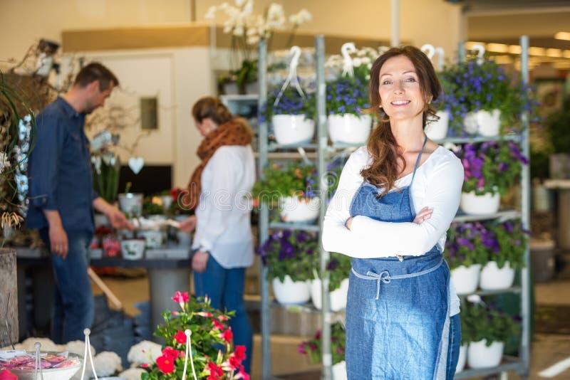 Porträt des lächelnden weiblichen Inhabers im Blumenladen stockfoto