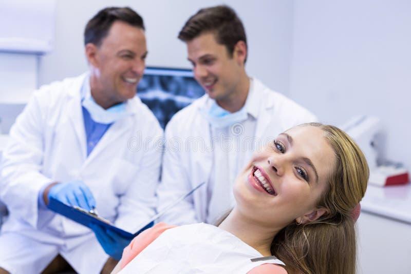 Porträt des lächelnden weiblichen Patienten, der auf zahnmedizinischem Stuhl sitzt lizenzfreie stockfotografie