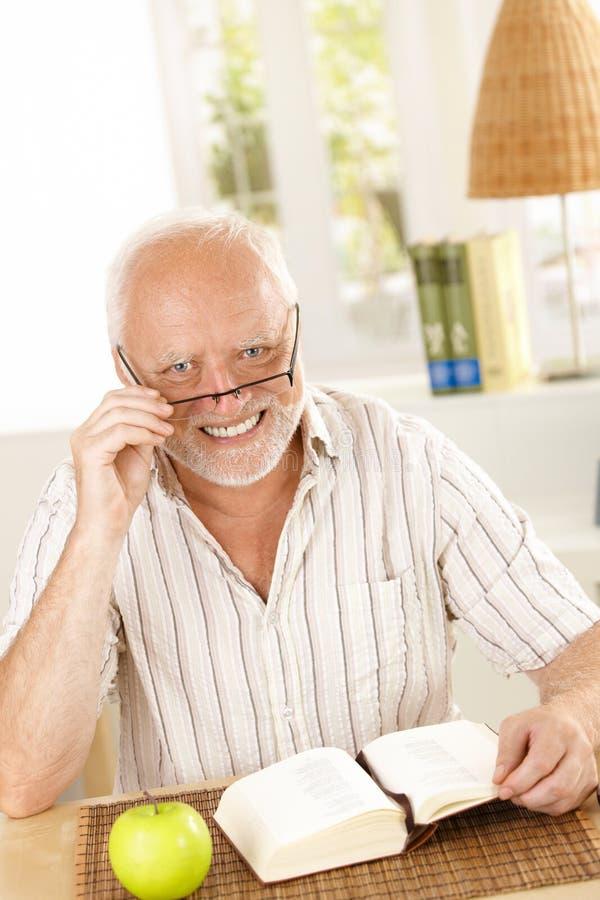Porträt des lachenden Seniors mit Buch stockfotos