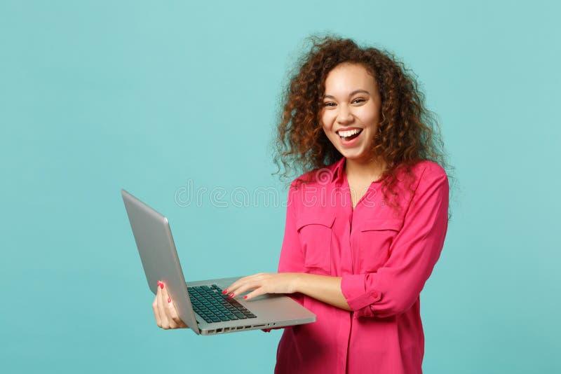 Porträt des Lachens des afrikanischen Mädchens in der rosa zufälligen Kleidung unter Verwendung des Laptop-PC-Computers lokalisie stockfotografie