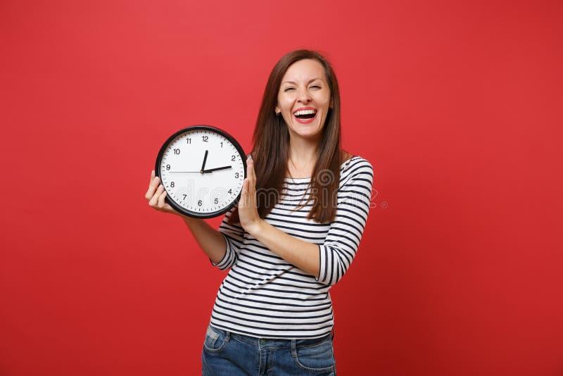 Porträt des Lachens der jungen Frau in der zufälligen gestreiften Kleidung halten runde Uhr lokalisiert auf hellem rotem Wandhint stockfotografie