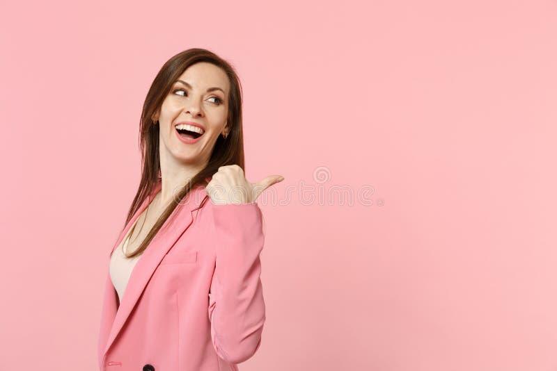 Porträt des Lachens der lustigen tragenden Jacke der jungen Frau, die, den Daumen zeigend beiseite lokalisiert auf rosa Pastellwa stockfotos