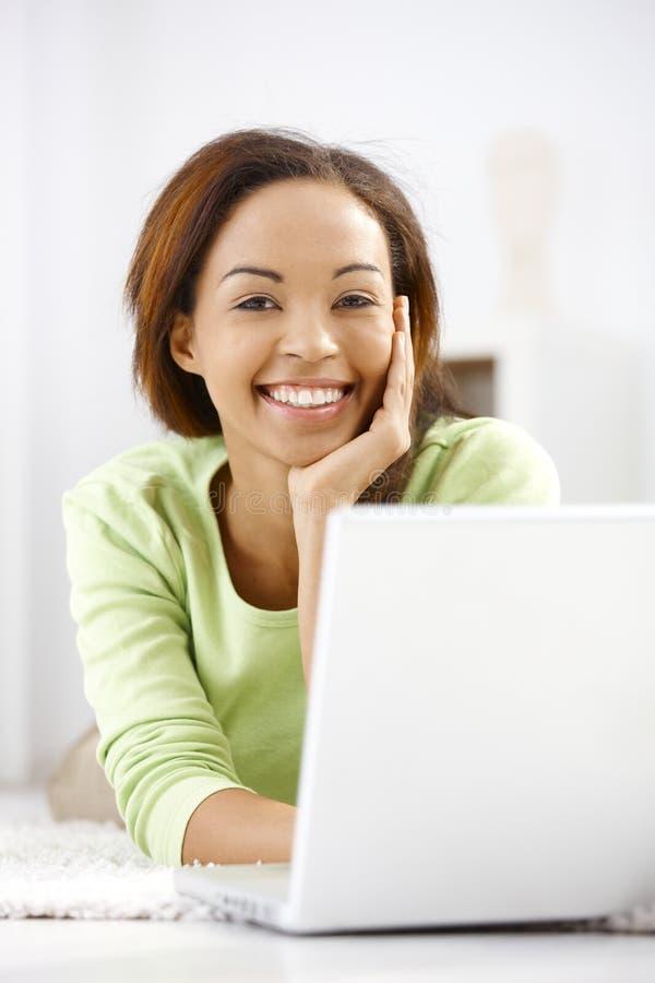 Porträt des Lachens des ethnischen Mädchens mit Laptop stockfotos