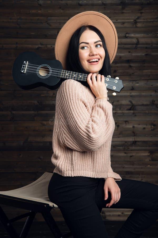 Porträt des Landhausstilmädchens aufwerfend mit ihrer kleinen Gitarre auf einem Stuhl lizenzfreie stockbilder
