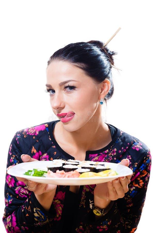 Porträt des Leckens der Lippenschönen jungen Frau, die den Spaß sitzt am Tisch und hält Sushiplatte hat lizenzfreie stockbilder